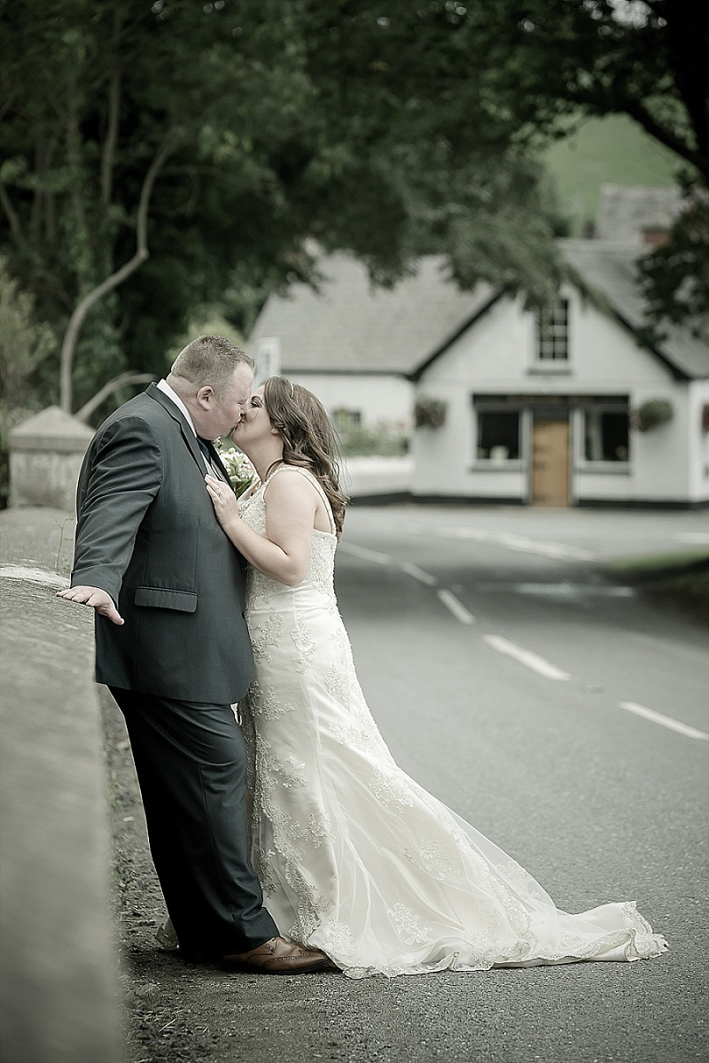 Bride and Groom Kissing Against a Wall