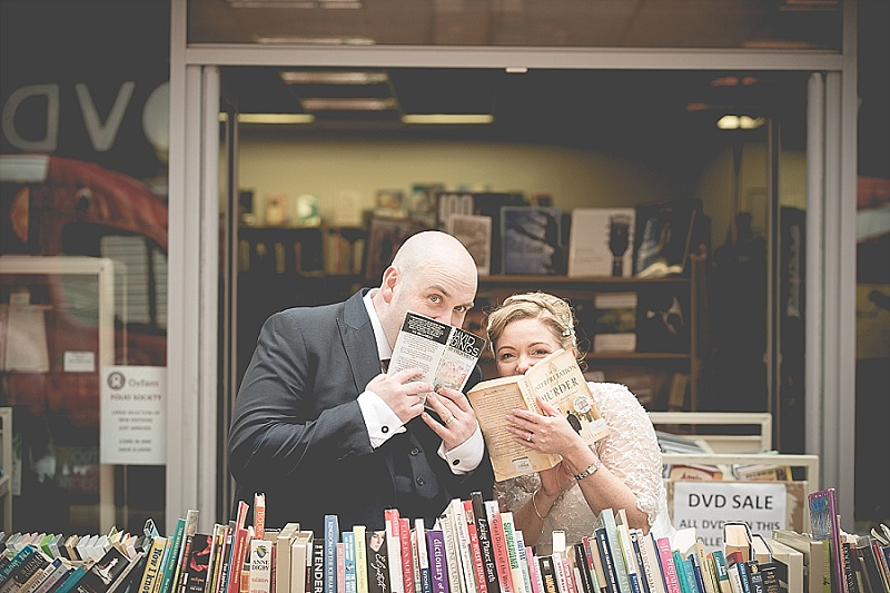 Bride and Groom hiding behind books outside book store