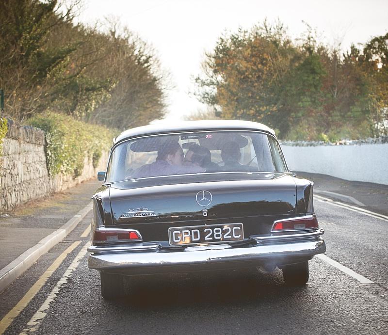 Bride and Groom in back of Vintage Car