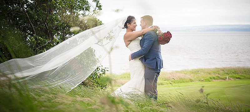 Bride and Groom on Grass Overlooking Sea