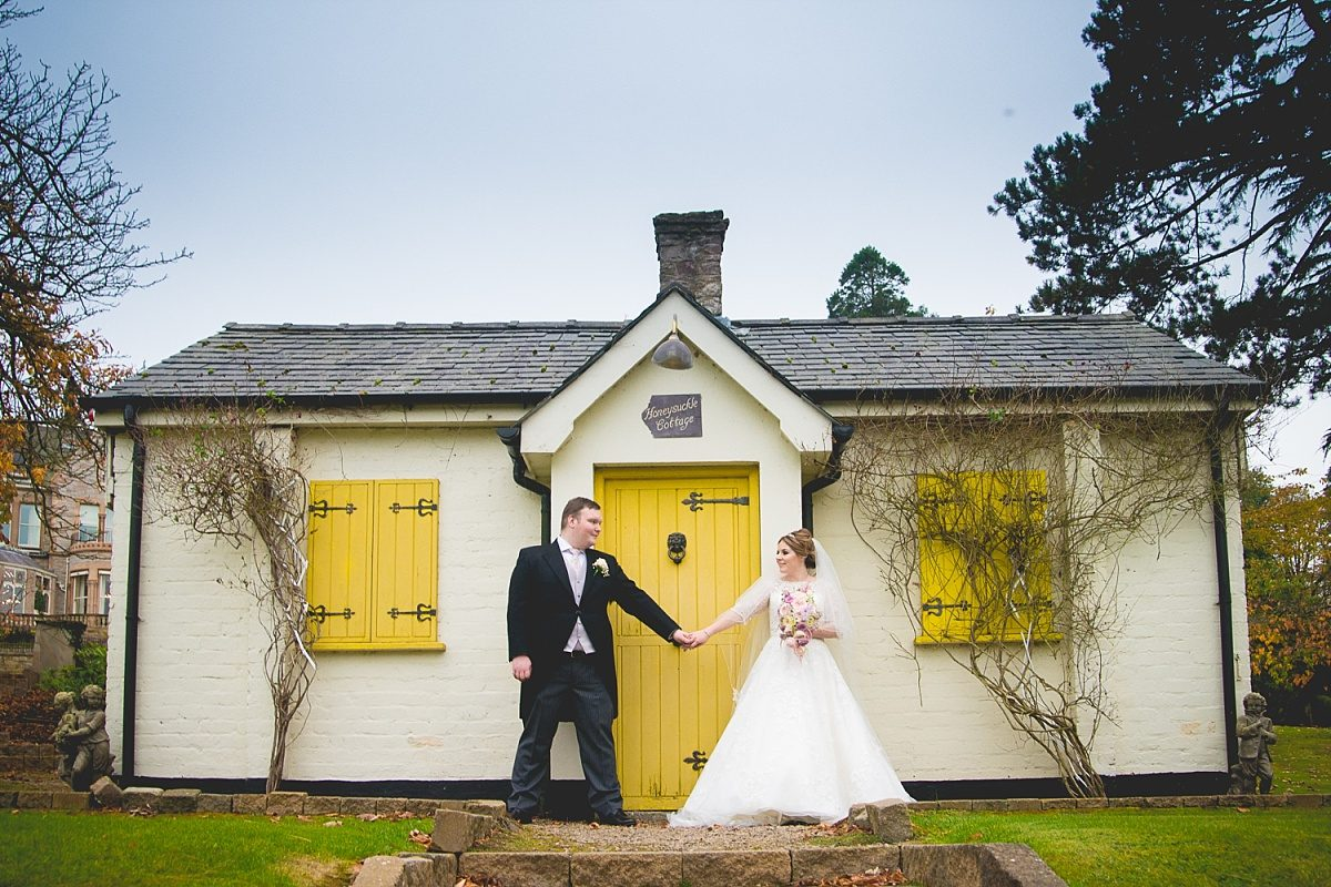 Bride and groom stand holding hands at the Culloden Hotel in front of the yellow door