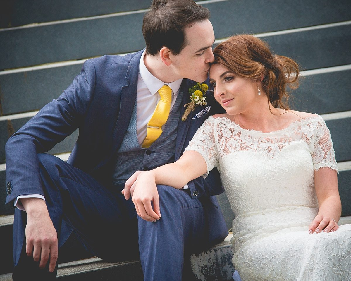 Bride and groom sit at Ulster Museum steps