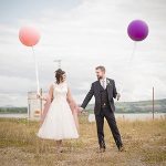 Alternative wedding couple with short dress and balloons