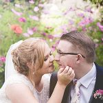 Bride and groom kiss with flare in background and spring colours