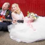 Bride and groom sitting jamming on the ground with guitar