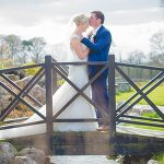Bride and groom stand on a wooden bridge on their wedding day