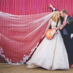 Bride and groom with guitar kiss against rustic gate