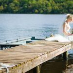 Bride in white dress sits on pier in summer weather with feet in the water