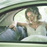 Bride sits on her own in a vintage car in the rain