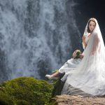 Bride sits on waterfall holding her veil at Glenoe Waterfall