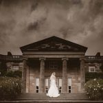 Bride stands on steps of Royal Historic Palace Hillsborough Castle with a dark moody sky