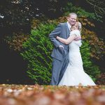 Couple kiss on their autumn wedding day