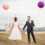 Couple standing with large balloons on their wedding day