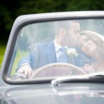 Husband and wife sit in vintage car on their wedding day
