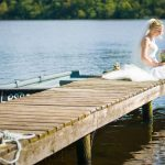 Bride sitting with feet in water on jetty
