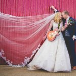 Vibrant bride and groom against red gate with guitar