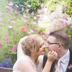 Wedding couple sit and kiss with lens flare