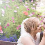 Couple kiss in the sunshine on a summer wedding day