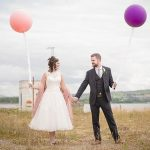 Bride anf groom with balloons celebrating