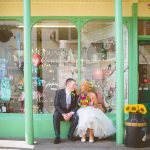 Rustic themed wedding with bride and groom sitting outside vintage shop
