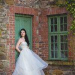 Bride stands in rain in wedding dress