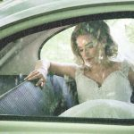 Bride sits in vintage wedding car