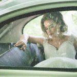 Bride sits in vintage wedding car