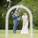 Bride and groom play croquet on their wedding day