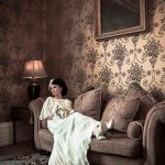 Classical bride sits on sofa with feet up in Gatsby dress
