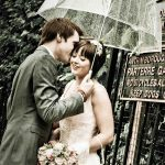 Wedding couple kiss in the rain under an umbrella