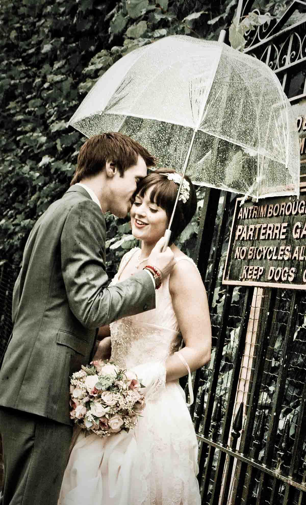 Wedding couple kiss in the rain under an umbrella