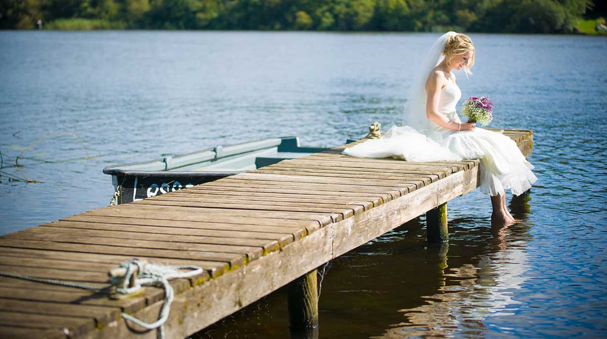 Bride sitting with feet in the water at Crom Castle