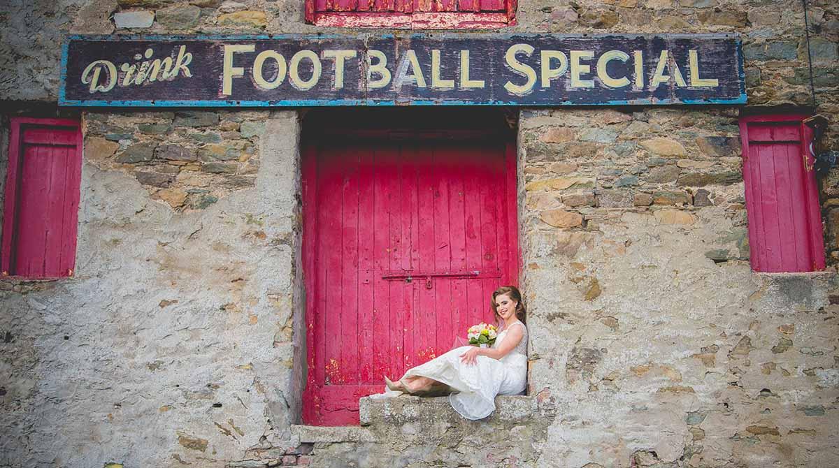 Bride sits in rustic doorway with paint peeling in Ramelton