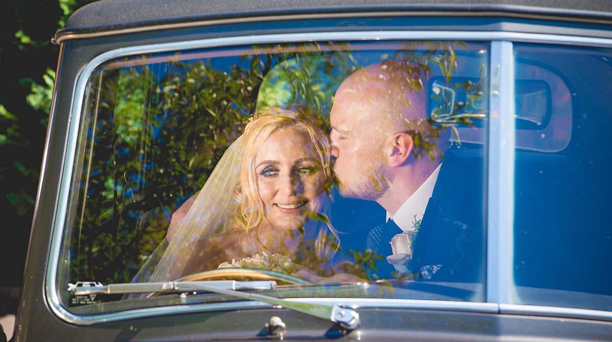 Bride and groom sit in wedding car in Bangor