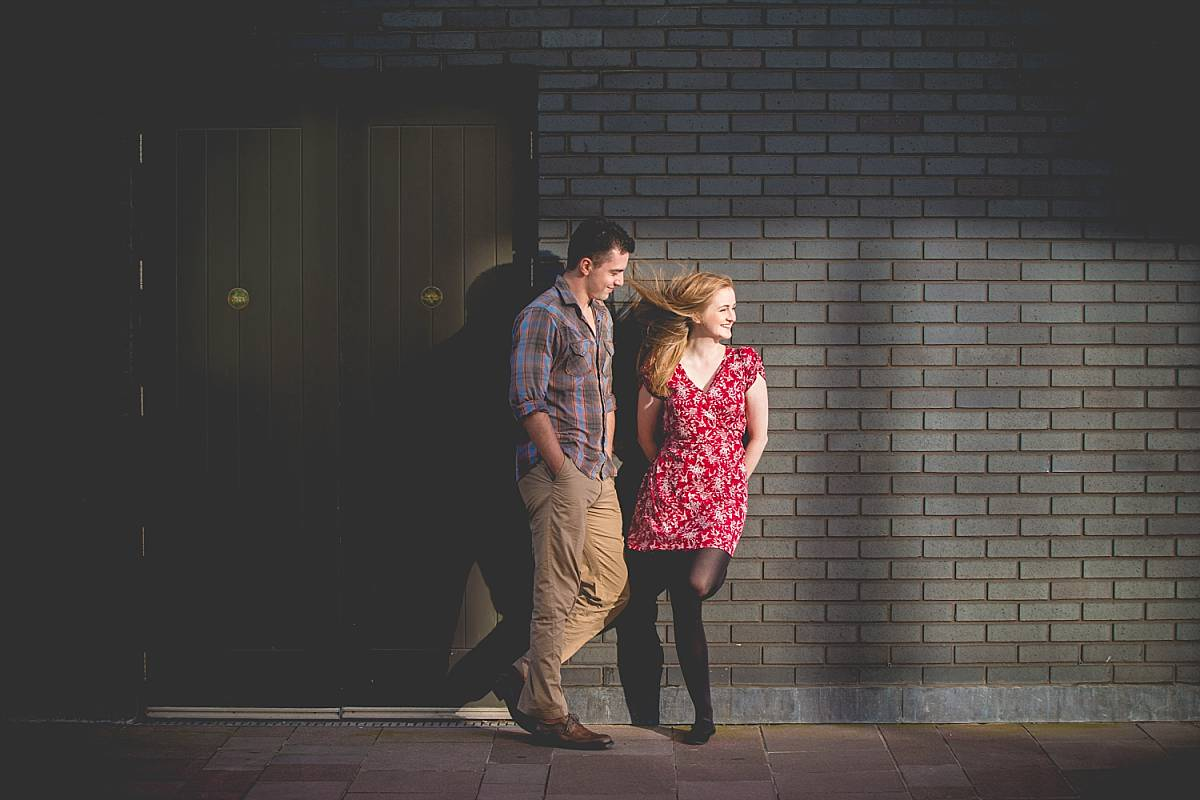 couple Leaning against a wall in shadow