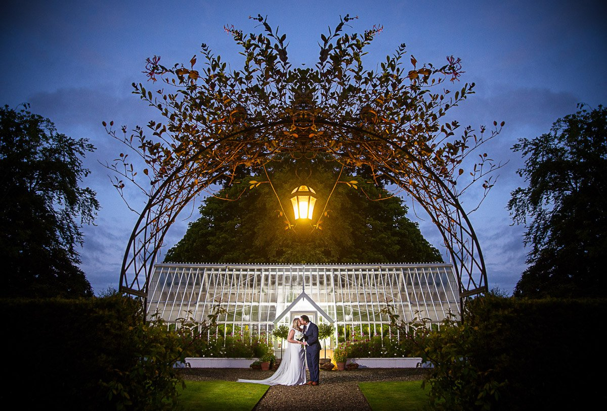 Bride and groom kiss outside green house at night at Montalto Estate
